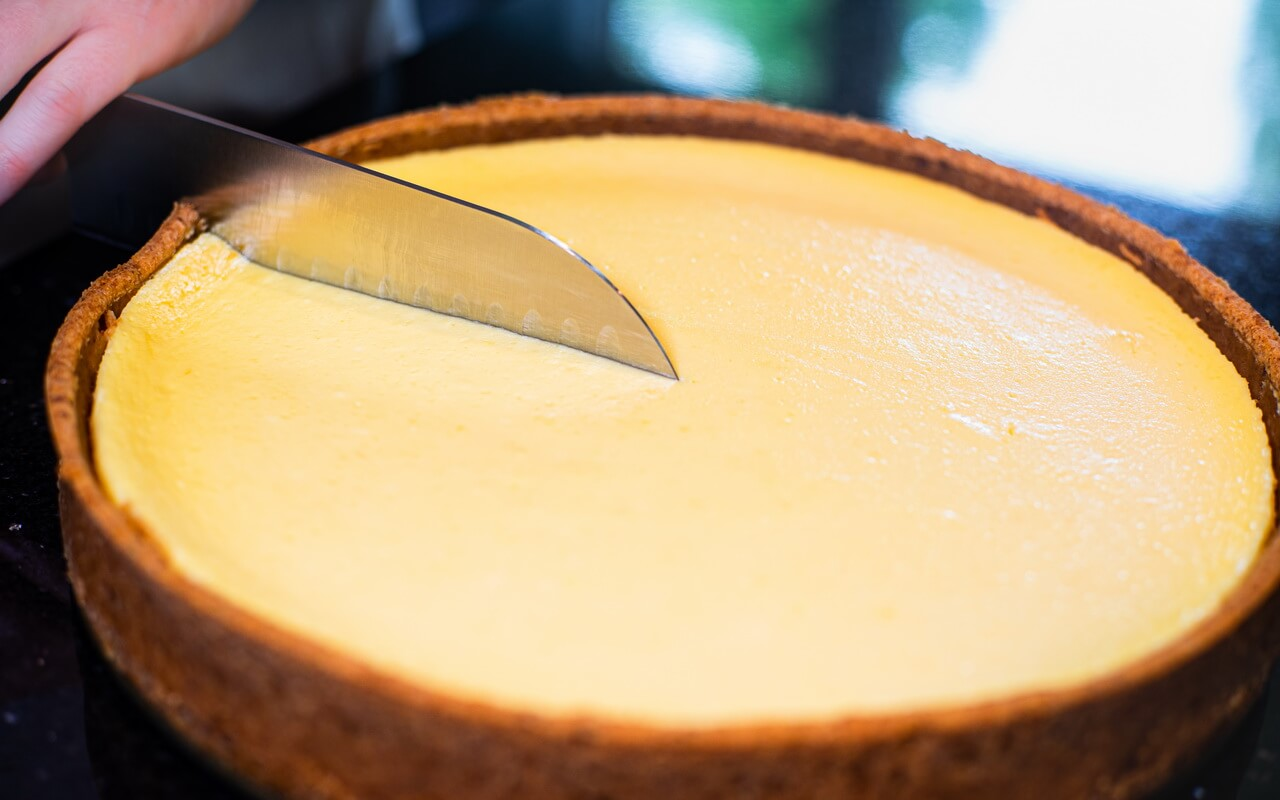 The Perfect New York Cheesecake Cutting Into Cake