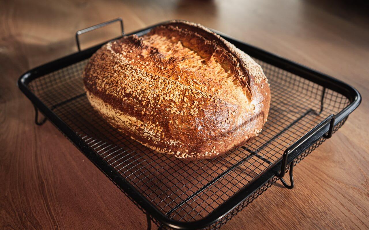 Sourdough Loaf With Sesame Seeds On Cooling Grid