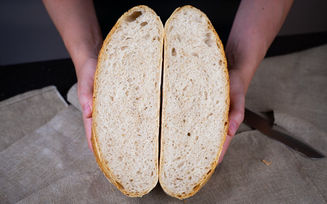 The Big Fluffy Round Sourdough Bread Holding Side By Side